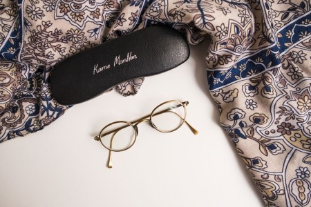 Blue patterned scarf, gold rimmed glasses