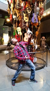 Antonio plays air guitar next to the musical instrument sculpture in the EMP museum.