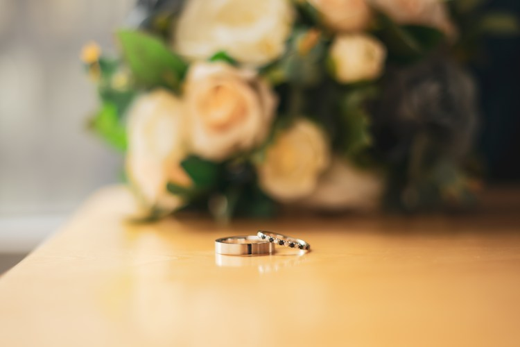 A photo of two wedding rings on a beige table. In the background and out of focus sits a bridal bouquet of flowers.