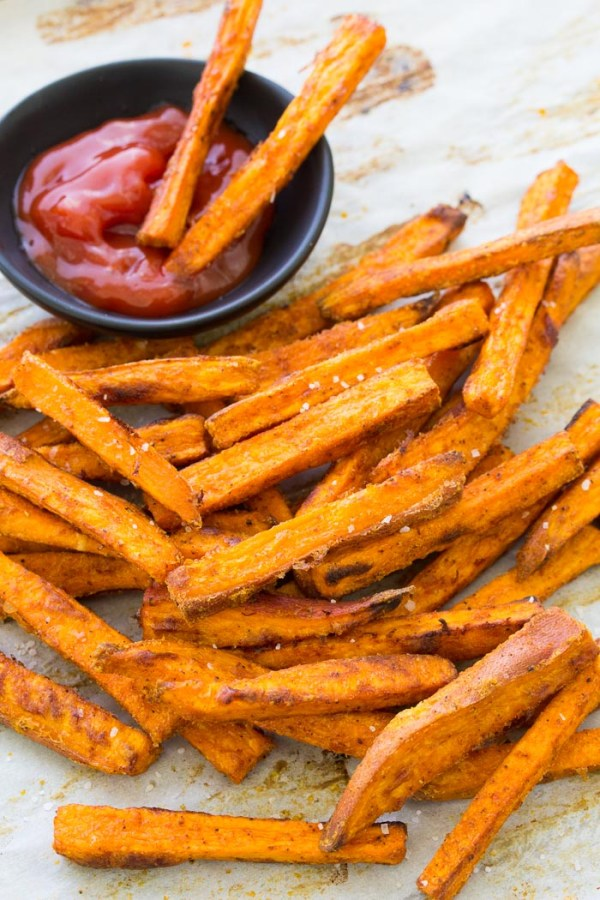 Sweet potato fries on a baking sheet, with two dipped in ketchup.