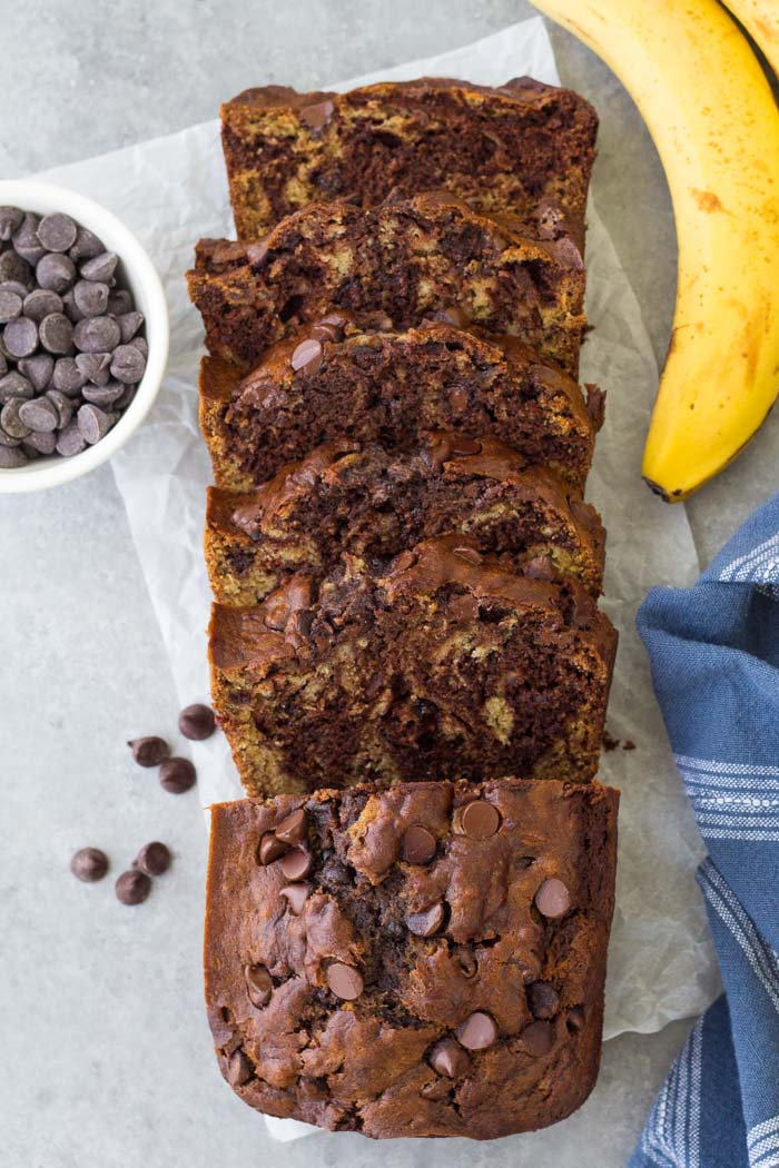 A loaf of chocolate banana bread, sliced with chocolate chips.