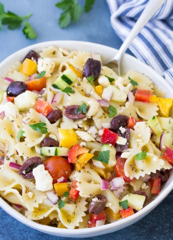 Greek pasta salad in a bowl with a serving spoon.