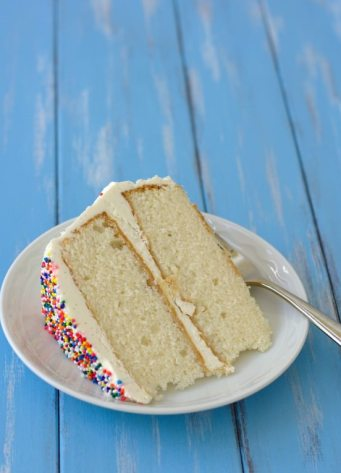 slice of white layer cake with sprinkles on a plate