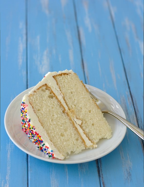 slice of two layered vanilla cake on a plate with sprinkles