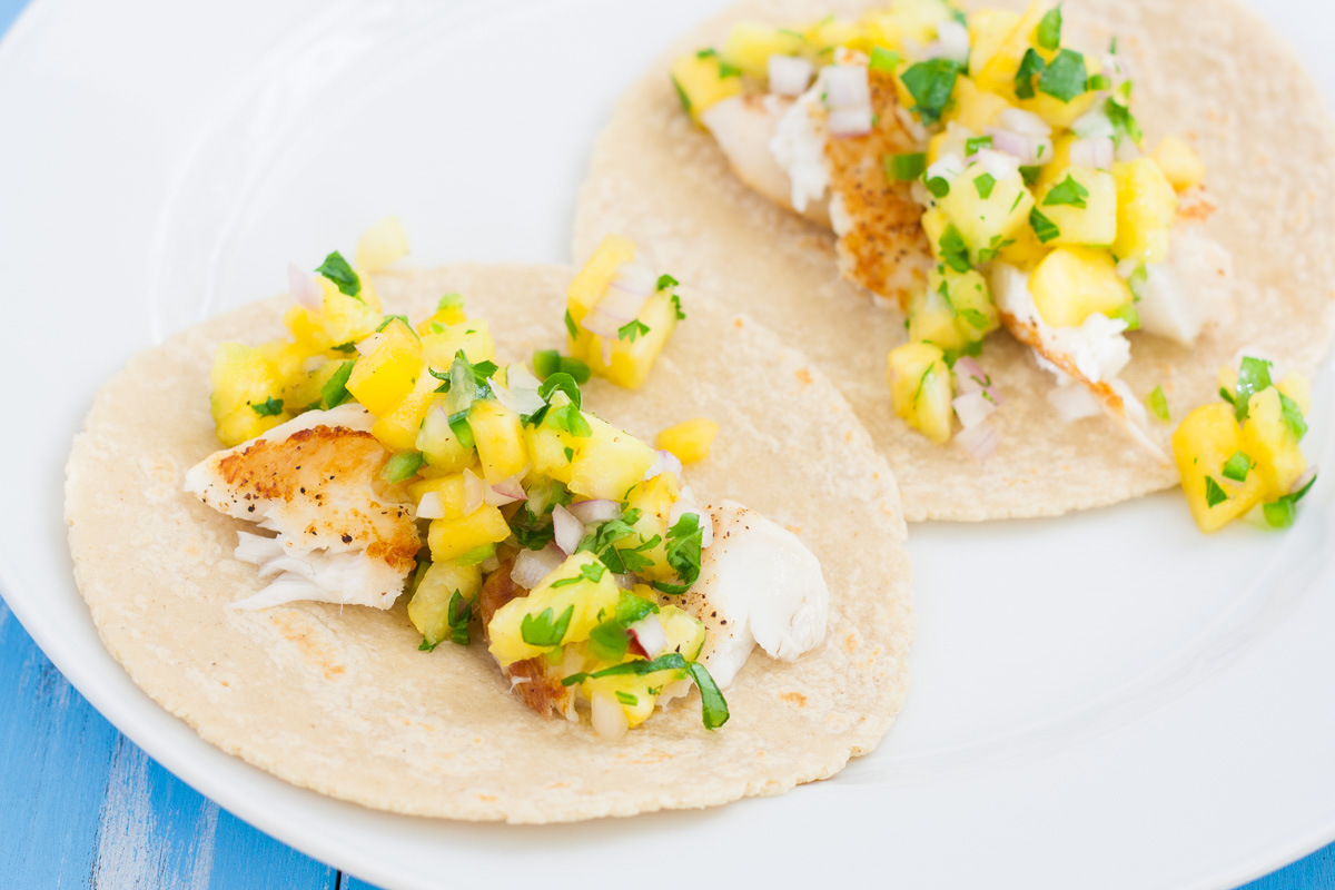 Two fish tacos topped with fresh fruit salsa.
