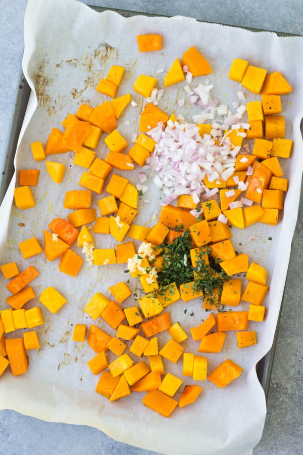 Roasted butternut squash with thyme and shallots on a sheet pan.