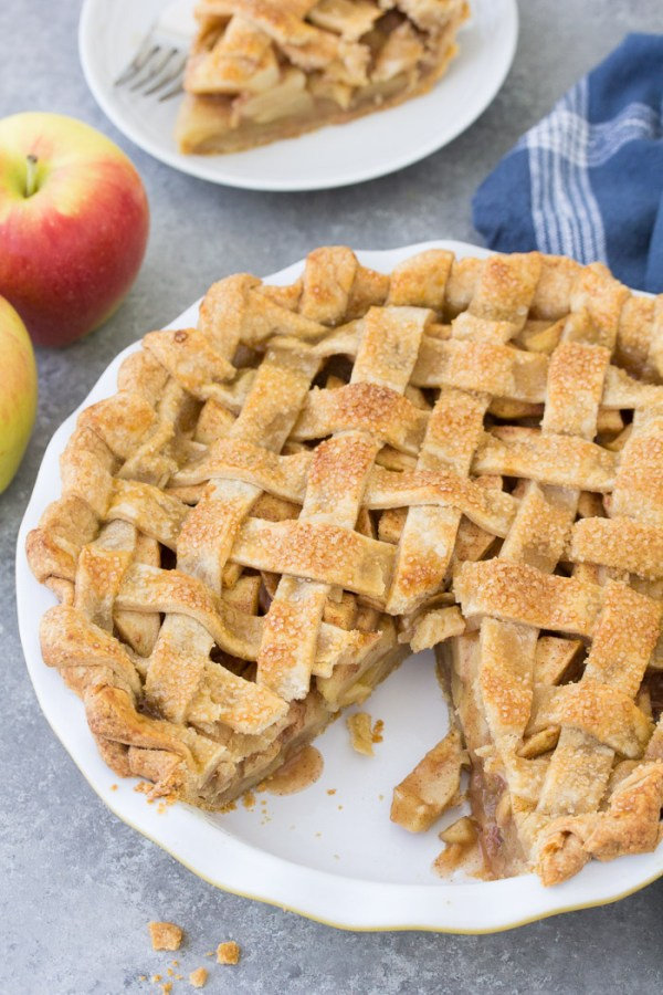 Whole apple pie with a slice cut out of it. A slice of pie and two apples in the background.