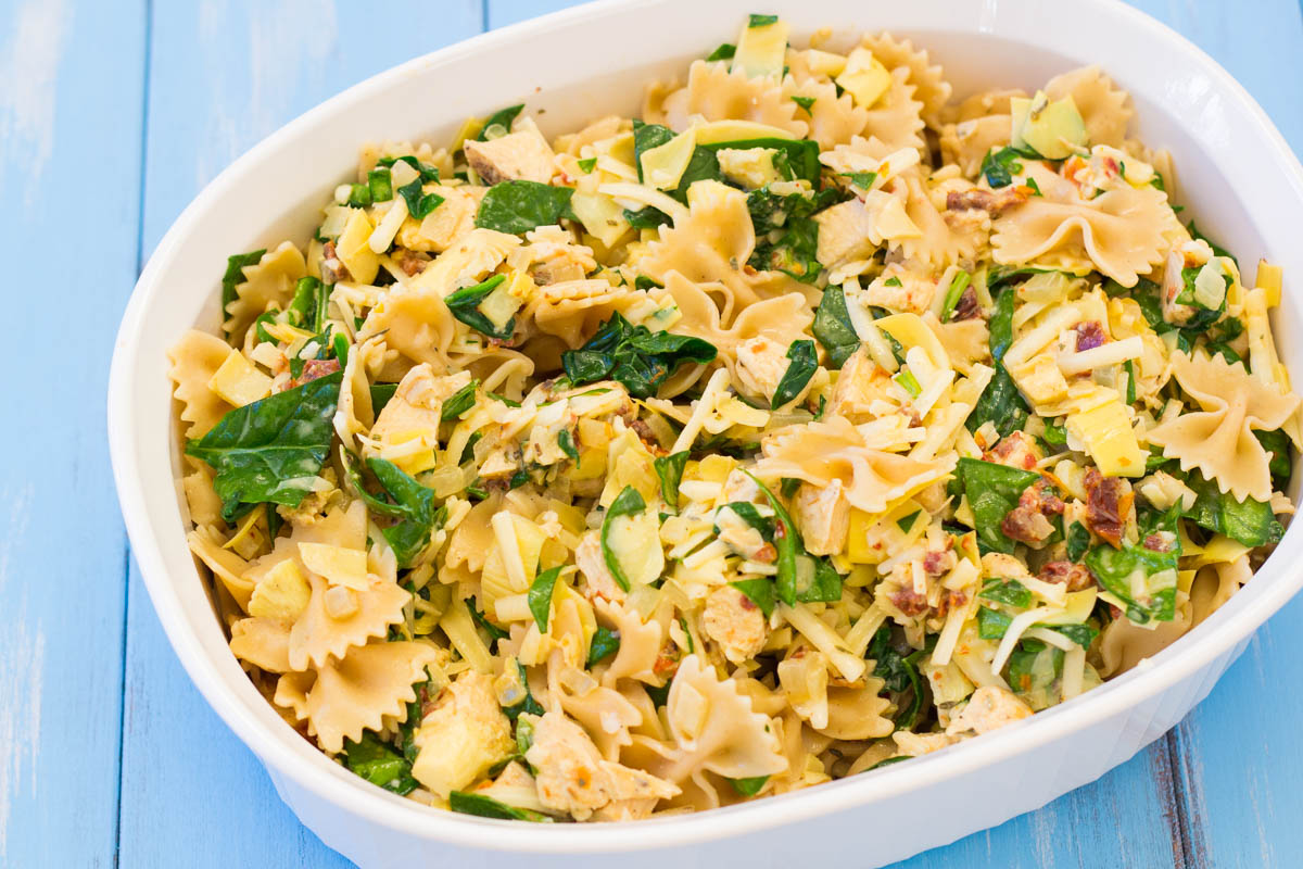 Chicken florentine pasta in a casserole dish with spinach and artichoke hearts.