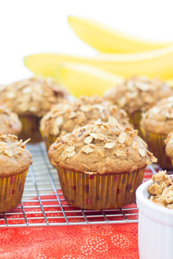 Side view of a muffin with crunchy granola on top and bananas in the background.