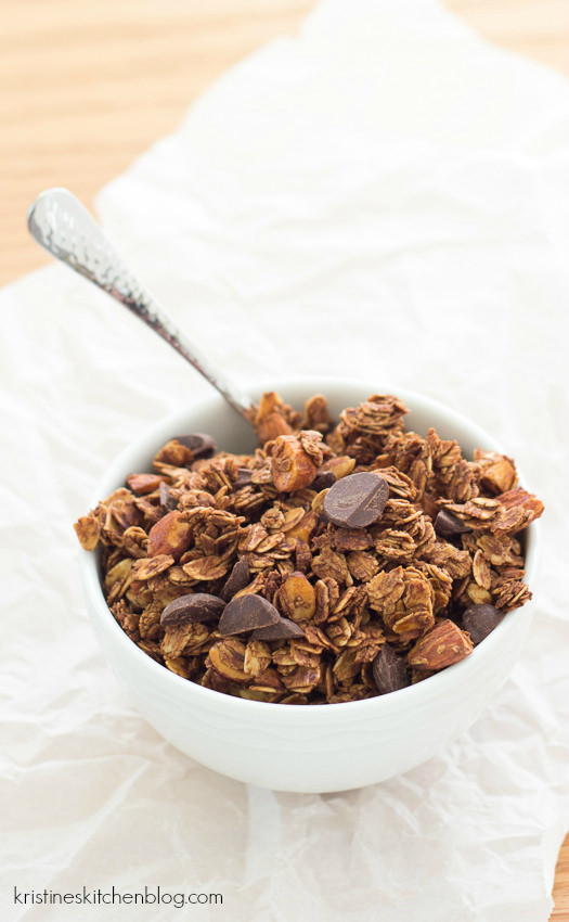 granola in white bowl with spoon