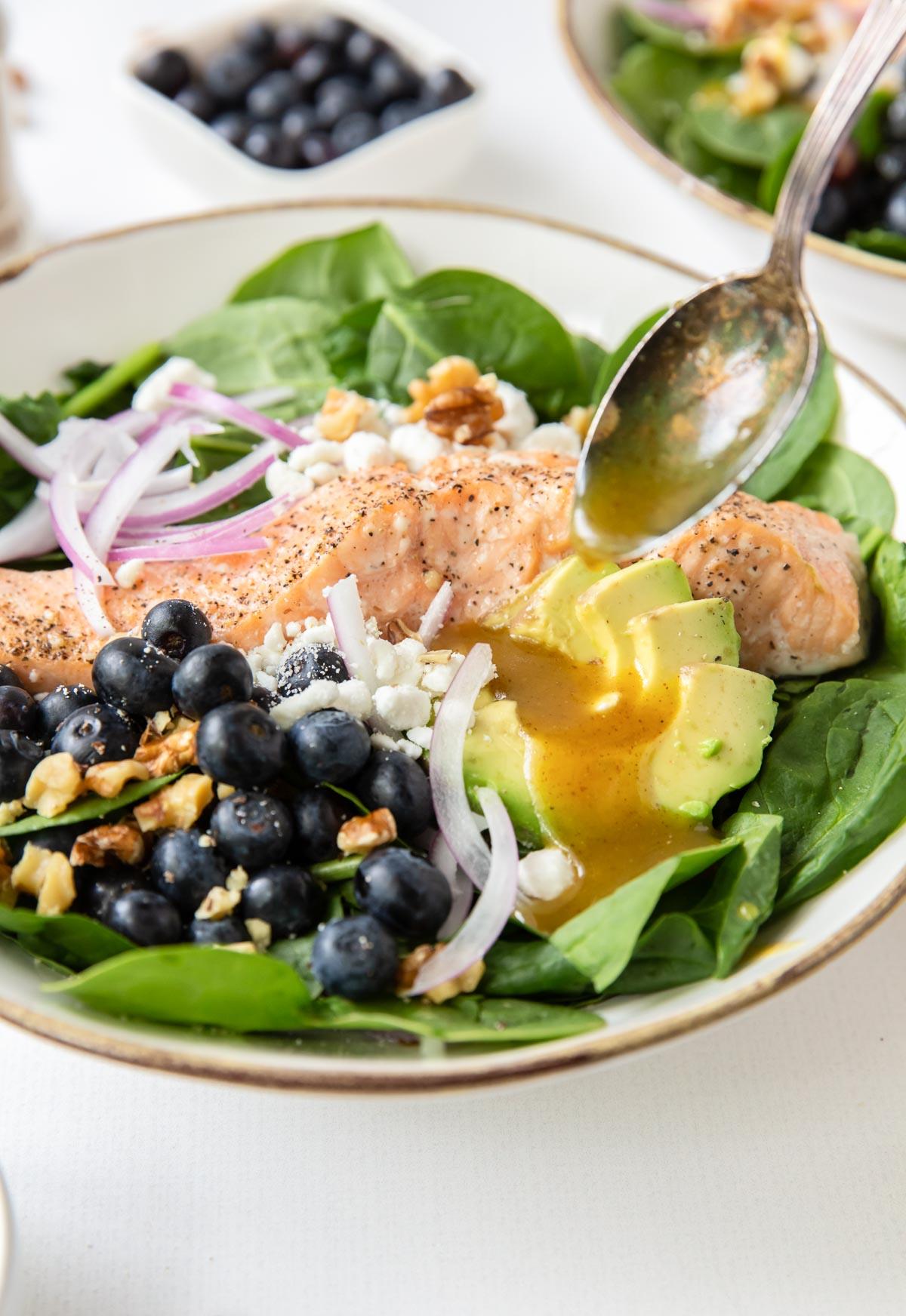 spooning honey mustard dressing onto salmon salad
