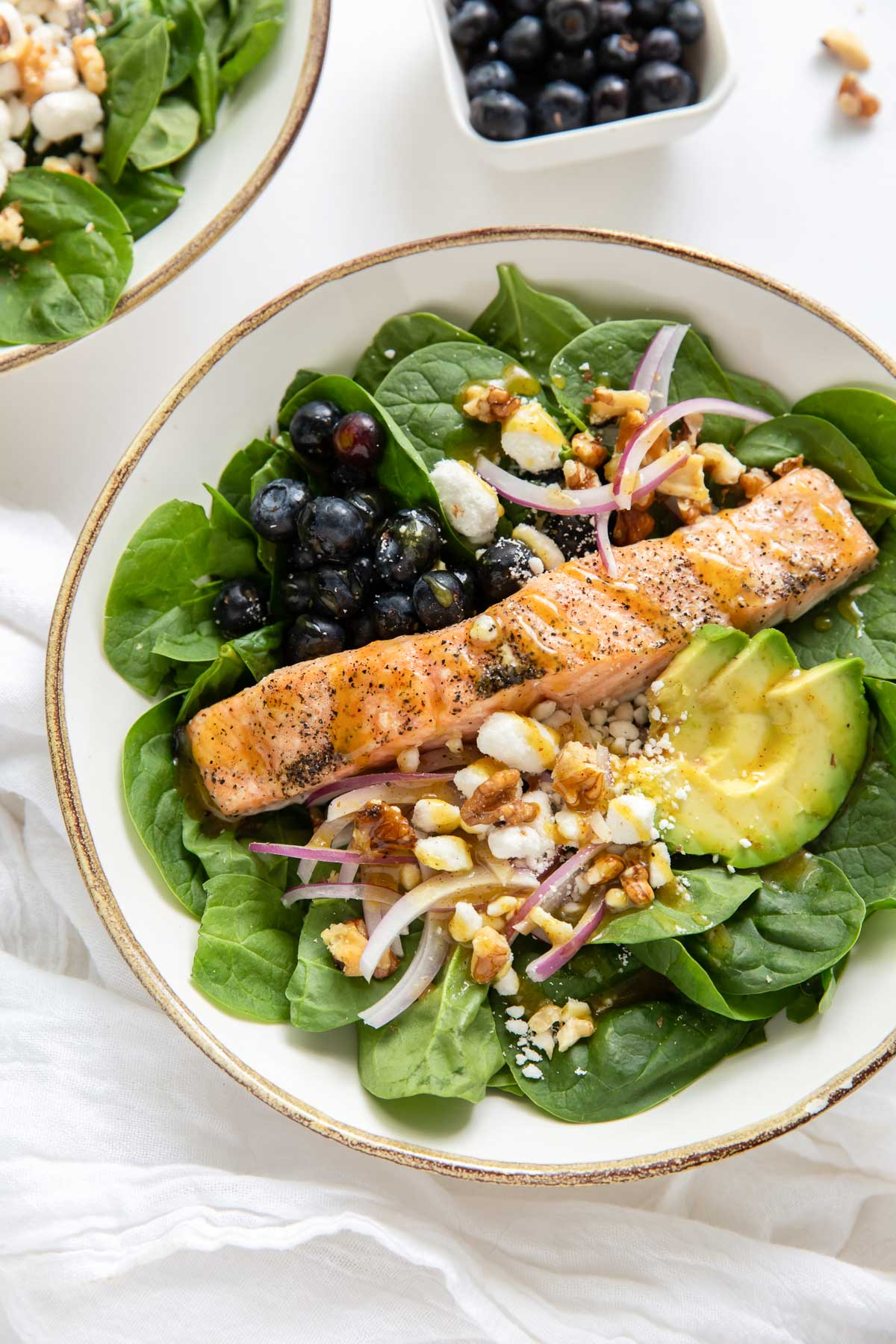 salmon salad with spinach, avocado, red onion, walnuts and goat cheese