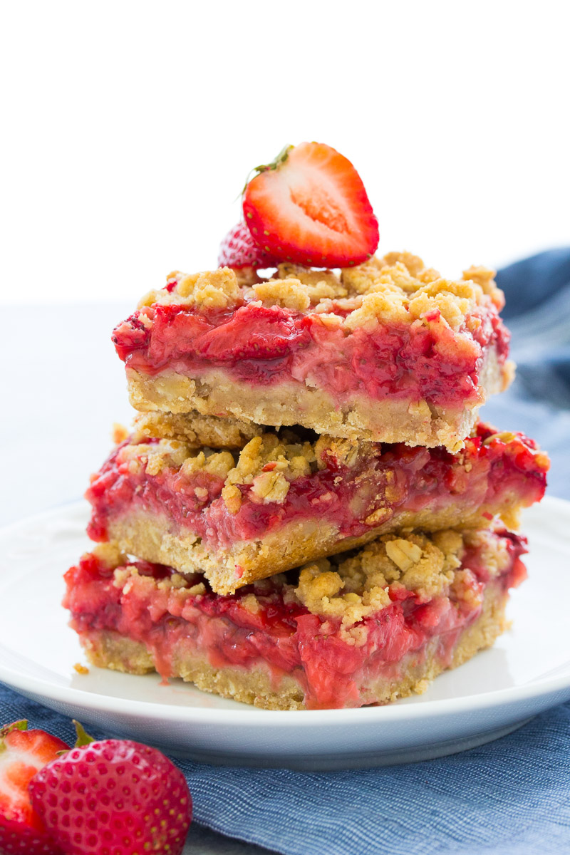 A stack of strawberry bars with oatmeal topping on a white plate with a fresh strawberry on top.