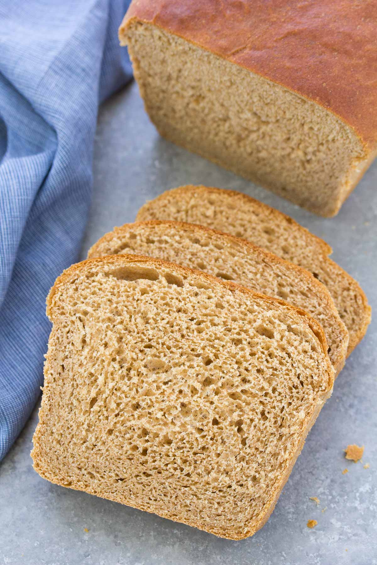 Three slices of homemade whole wheat bread with a loaf in the background.