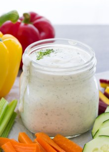 Side view of ranch dressing in a jar, surrounded by veggies.