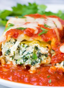 two cheesy spinach lasagna roll ups on a plate with marinara sauce