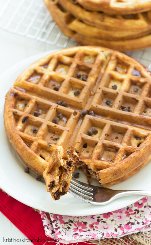 Close up picture of a chocolate chip waffle and a bite of waffle on a fork