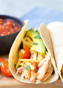 Close up side view of crockpot chicken tacos with salsa, avocado and tomatoes.
