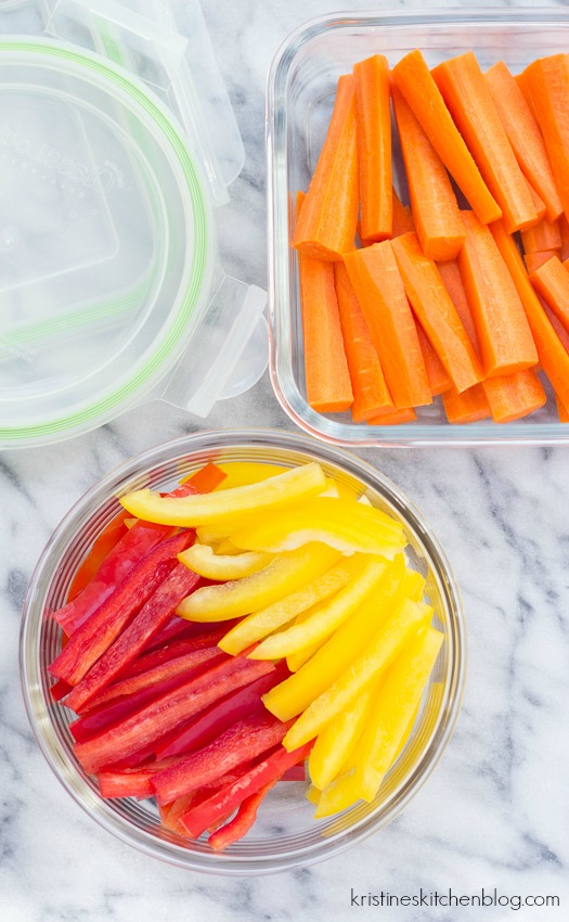 cut carrots and cut red and yellow bell peppers in clear storage containers
