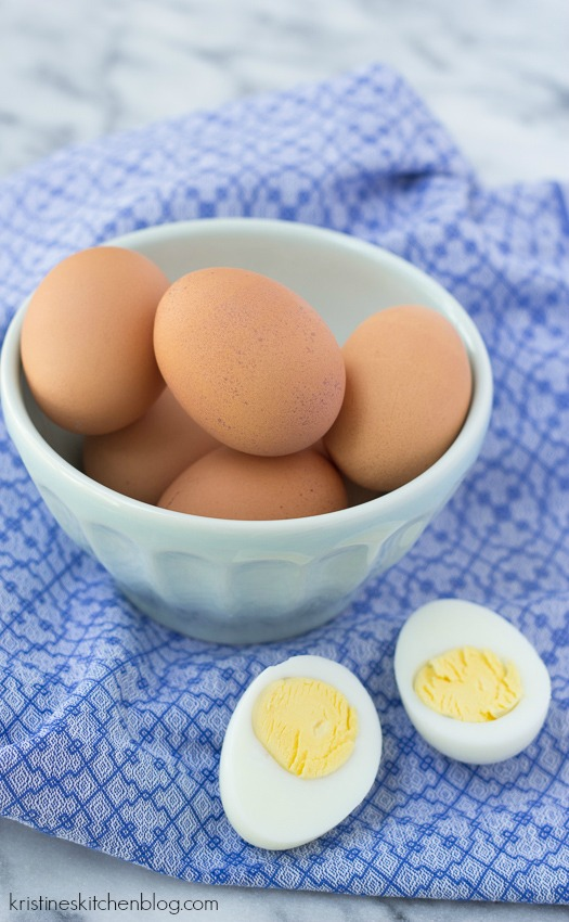 five brown eggs in a small bowl with one cut hard boiled egg in front