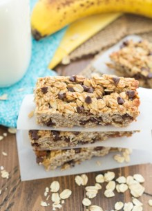 Banana chocolate chip granola bars stacked on top of each other with parchment paper in between.