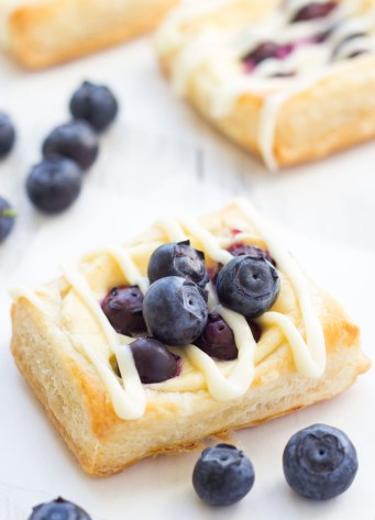 homemade cream cheese danish with icing and topped with blueberries
