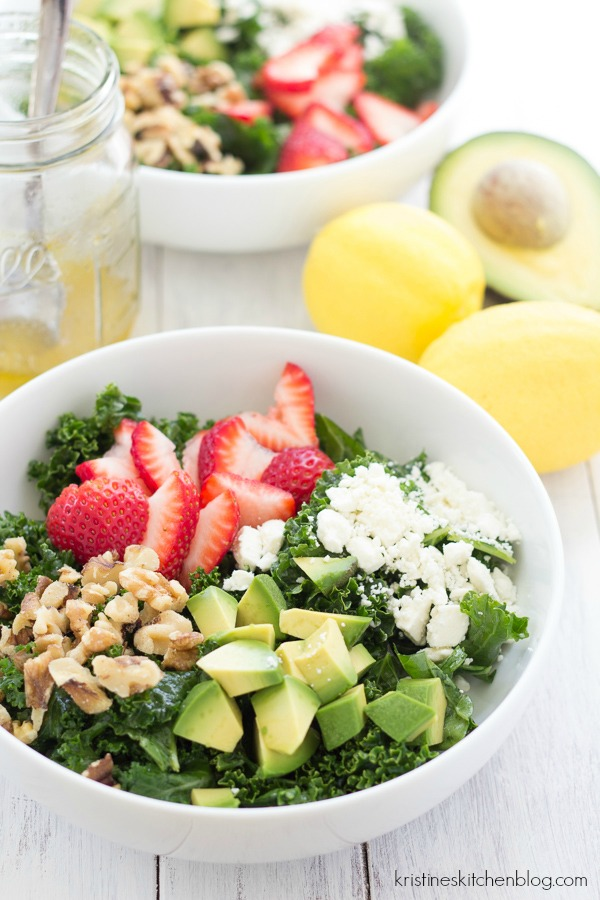sweet kale salad showing ingredients, strawberries, nuts, avocado, feta cheese, salad dressing