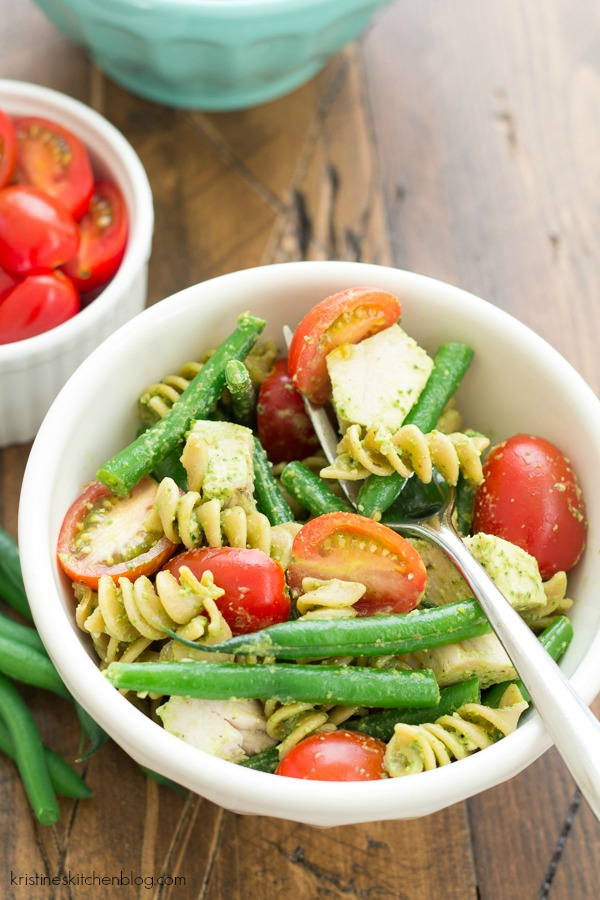 closeup of pesto pasta with chicken, tomatoes in a bowl with a fork
