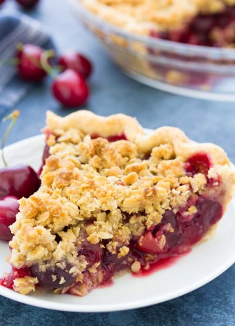 Slice of cherry pie with crumble topping on a white plate, with cherries and a whole pie in the background.