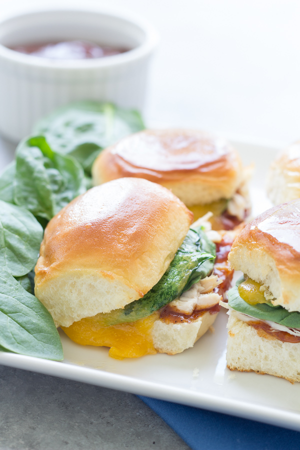 BBQ Chicken Sliders with Cheddar and Spinach. Tangy BBQ sauce, gooey cheddar and chicken make for one tasty little sandwich!