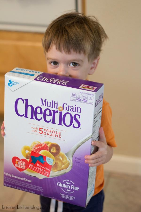 boy holding box of multi grain cheerios