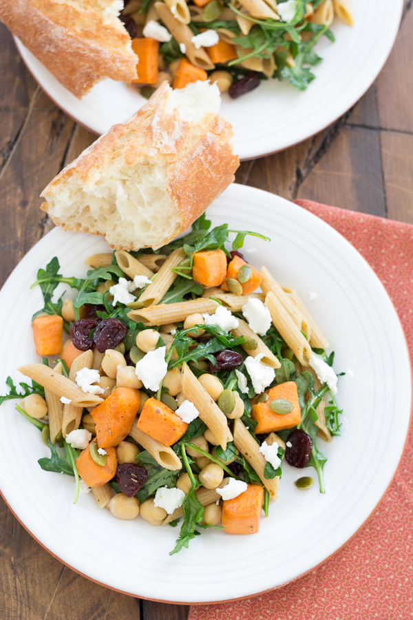 serving of pasta with sweet potatoes and arugula with side of bread