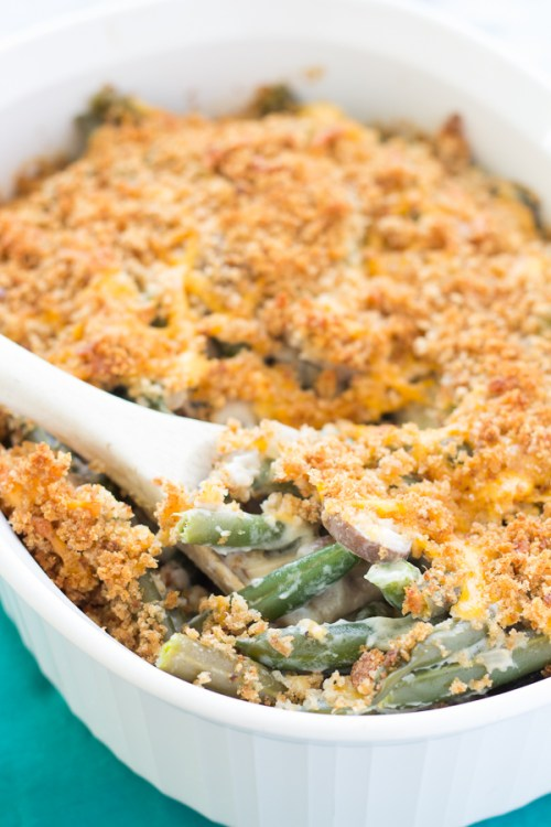 Green bean casserole from scratch in a white serving dish with a wooden spoon.
