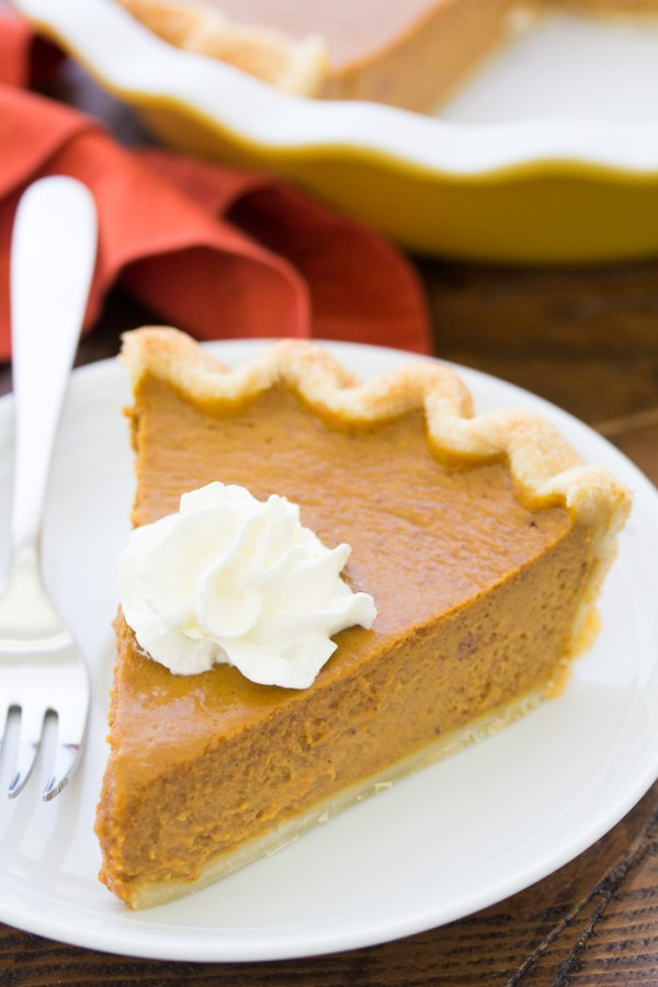 Side view of a slice of pumpkin pie served with whipped cream.