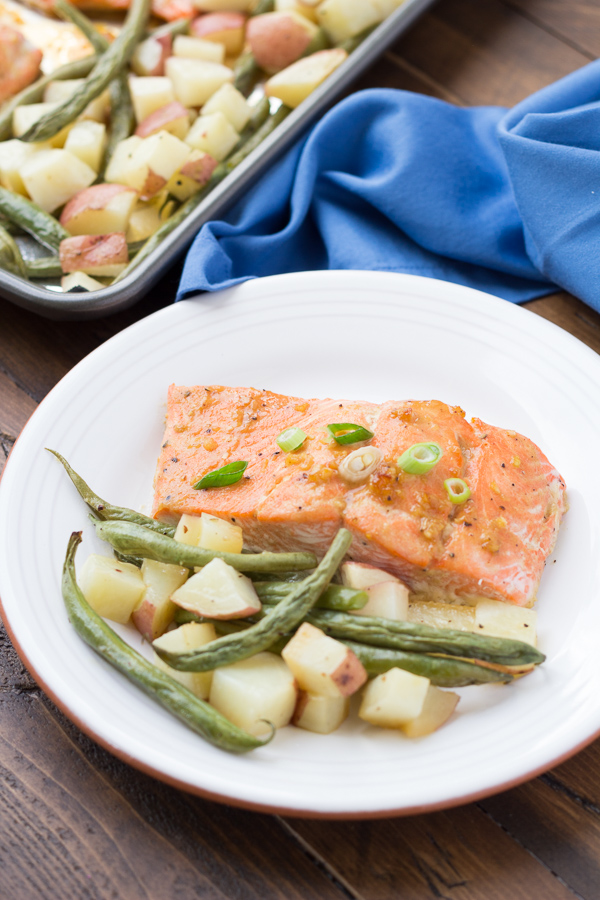 Baked Honey Garlic Salmon fillet on white plate with green beans and potatoes