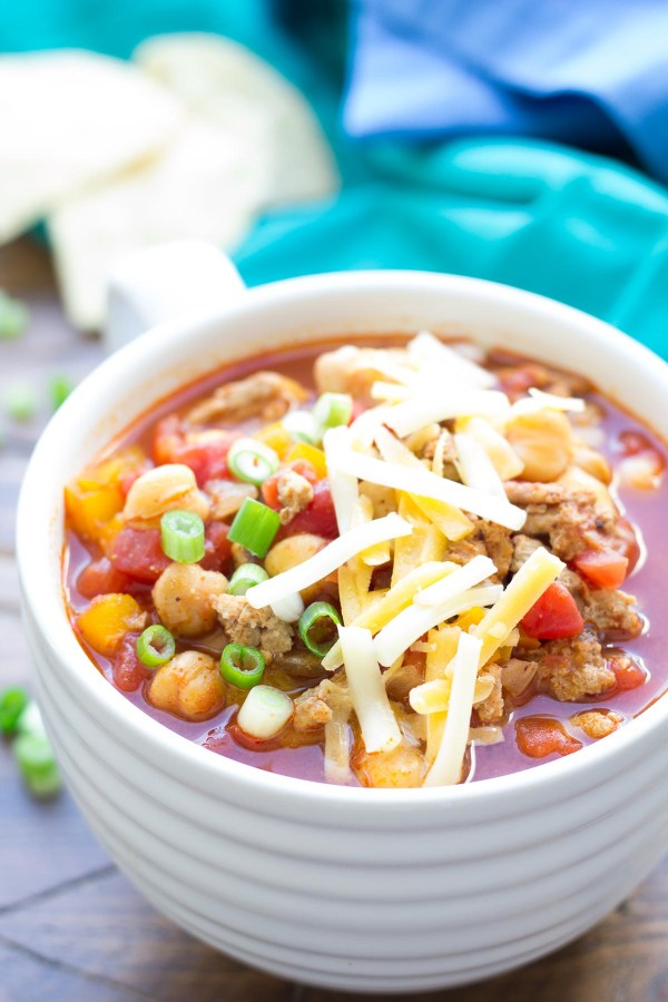Close up of slow cooker turkey chickpea chili in a bowl with shredded cheese on top.