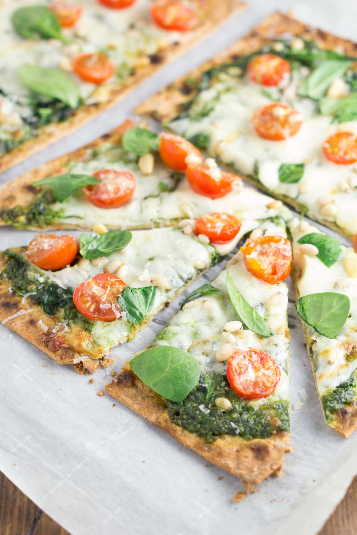 Spinach Pesto Pizza with Tomato on parchment paper