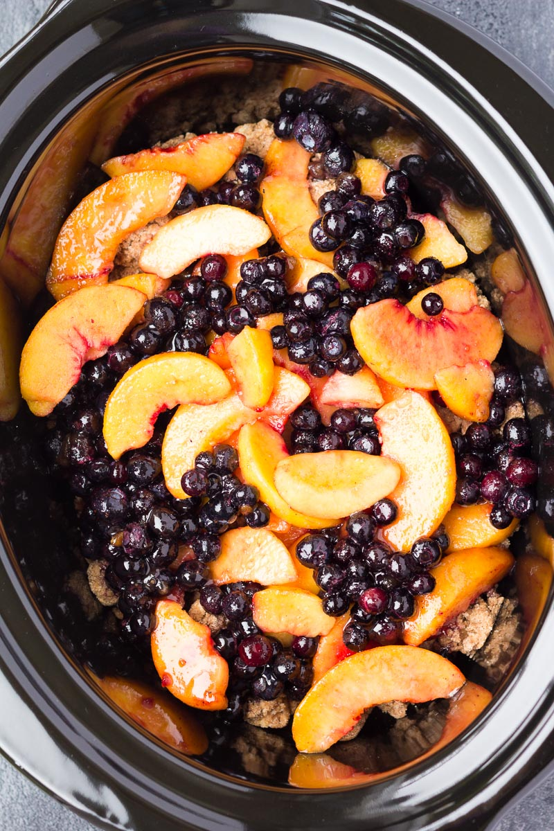 Ingredients for blueberry peach cobbler in a slow cooker.