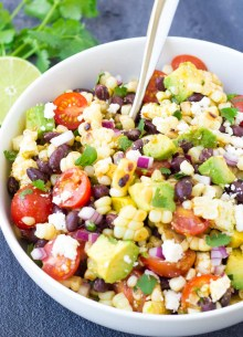 Corn salad with black beans, avocado and tomatoes in a white serving bowl with a spoon.