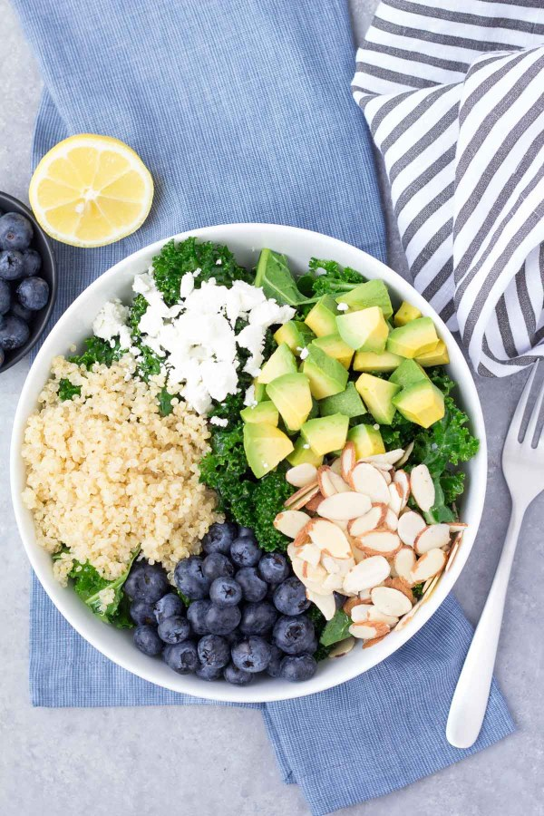 Kale Salad ingredients in white bowl including avocado, quinoa, blueberries, almonds and goat cheese.