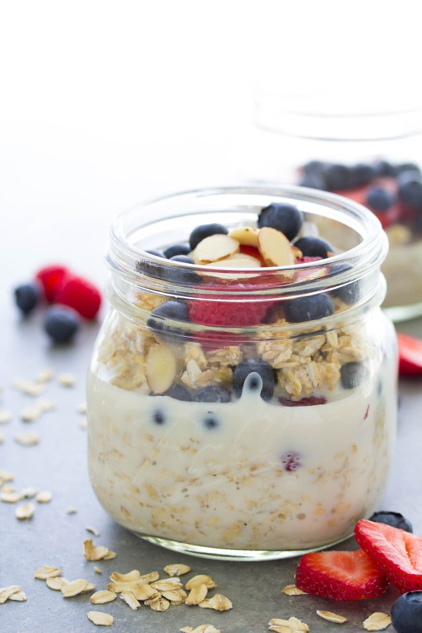 Side view of overnight oatmeal in a mason jar with strawberries, blueberries and almonds.