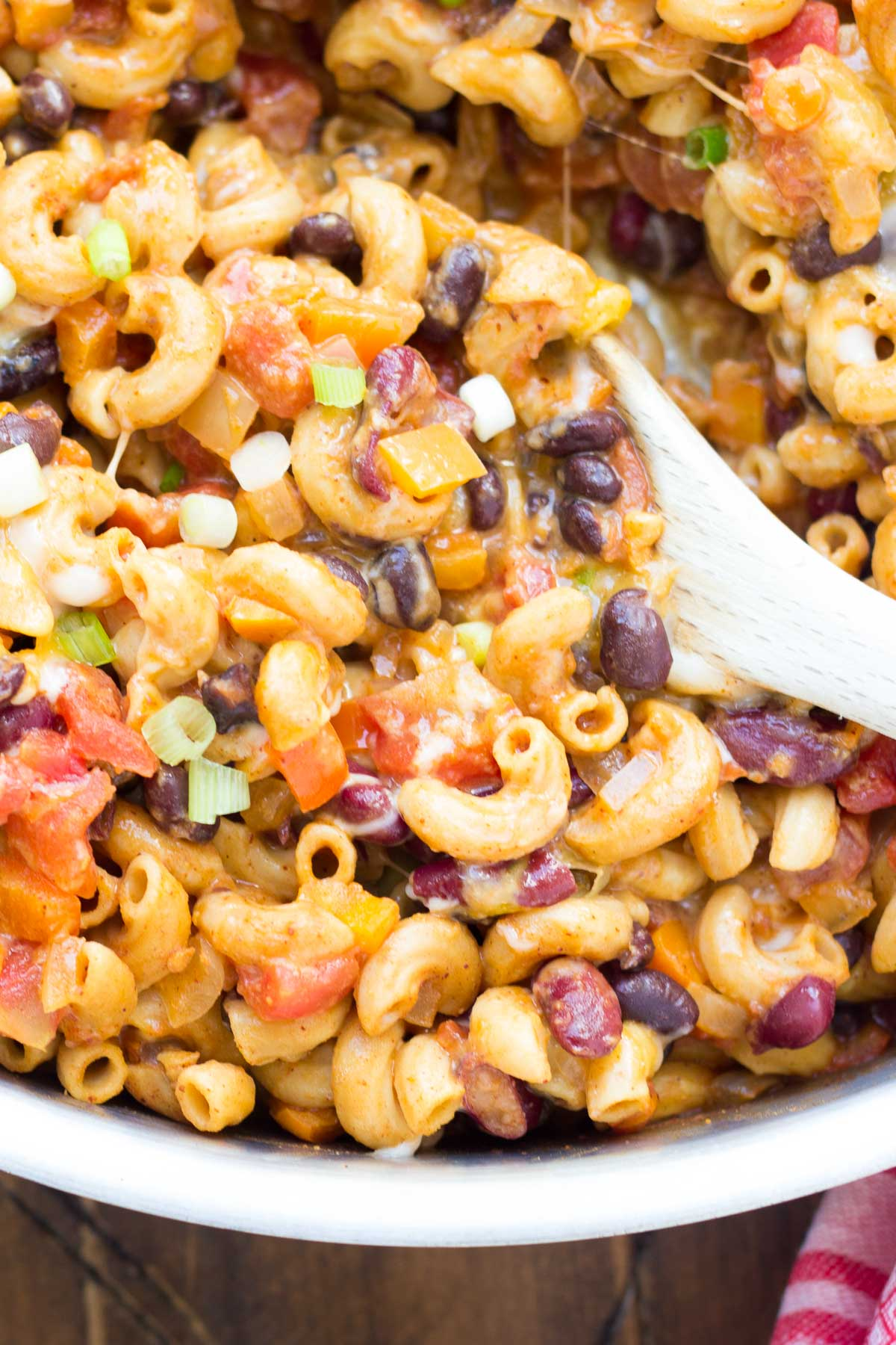 Vegetarian chili mac in a skillet with a serving spoon.