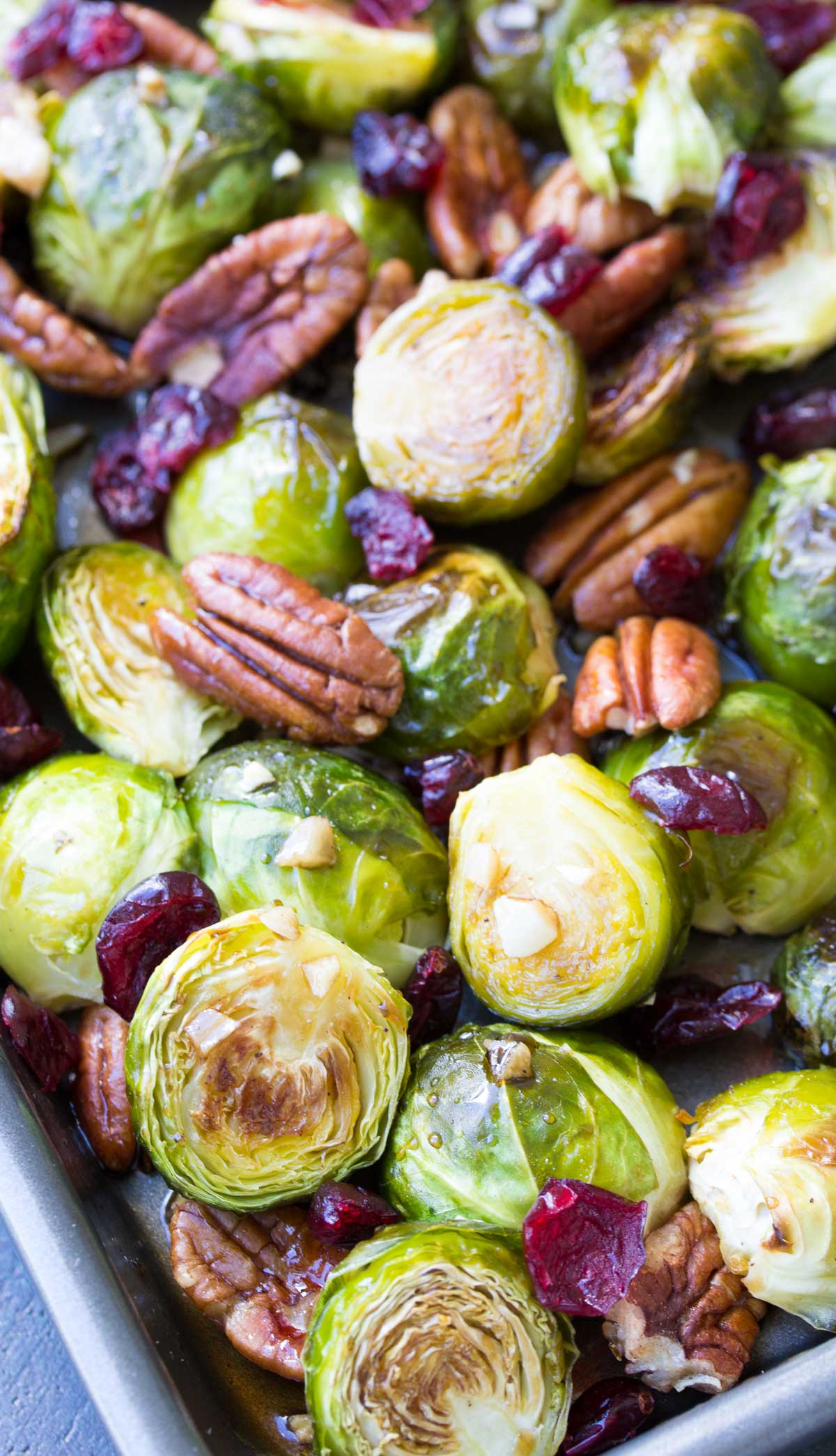 Balsamic Brussels Sprouts with garlic, pecans, cranberries and maple balsamic glaze on a baking pan.