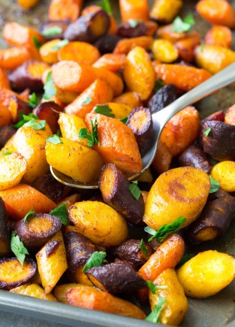 Close up of roasted carrots with a spoon on a baking sheet.