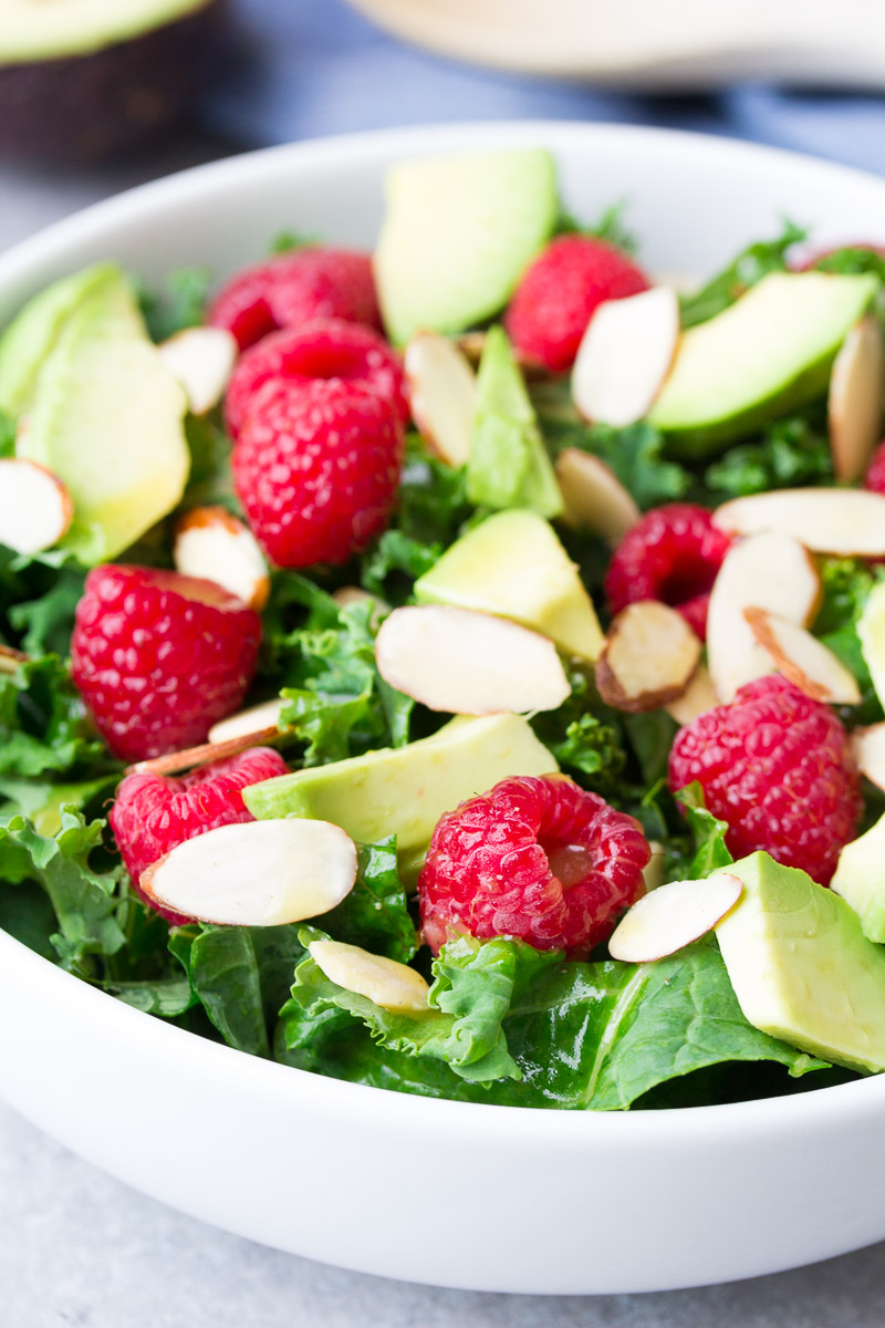 Close up of kale salad with avocado, raspberries and almonds.