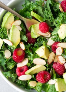 Kale avocado salad in a white bowl with a fork.