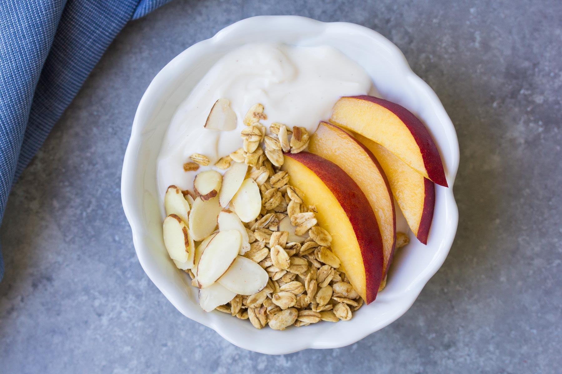 Peach Granola Yogurt Bowl. Diary free, made with almond milk yogurt.