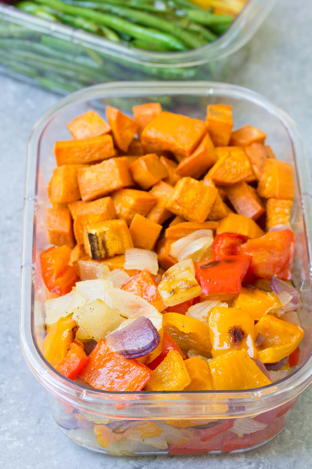close up of meal prep cubed sweet potato, onion and pepper in clear container