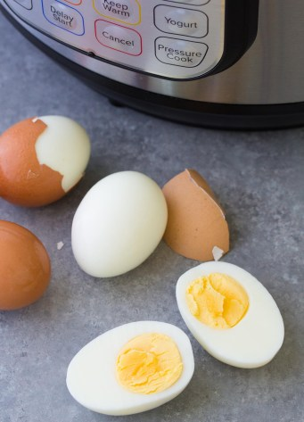 Instant Pot hard boiled eggs with the shells falling off and one cooked egg cut in half.