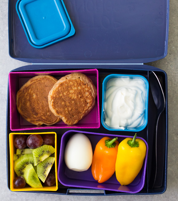 Kids lunch box with healthy carrot cake pancakes and maple yogurt for dipping.